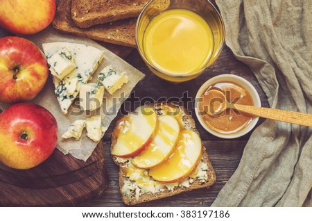 Toast with apple, honey and gorgonzola cheese on rustic wooden background. Healthy breakfast. - stock photo