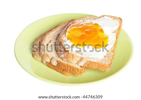 Toast with butter and peach jam in the green plate isolated on white background. Shallow depth of field
