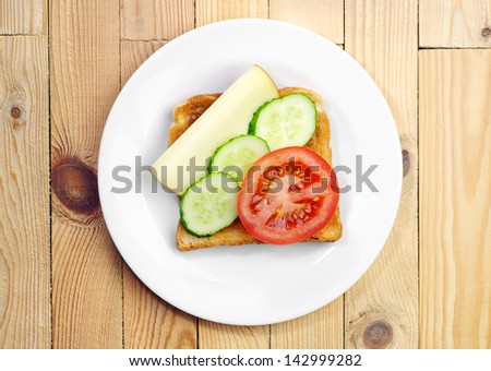 Toast with cheese, tomato and cucumber on a plate on the table. Top view  - stock photo