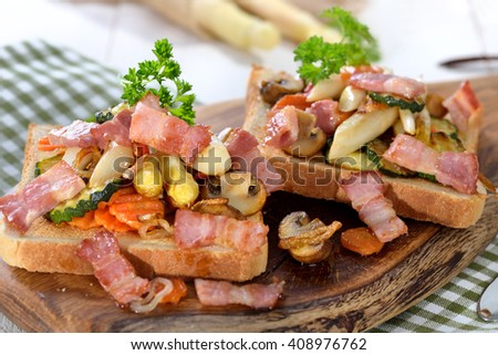 Toast with fried white asparagus, other vegetables and bacon strips, served on a wooden board