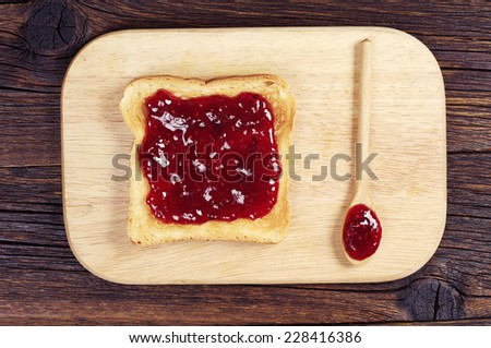 Toast with jam and spoon on cutting board. Top view - stock photo