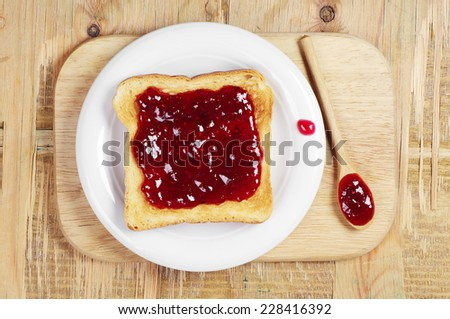 Toast with jam and wooden spoon on cutting board. Top view - stock photo