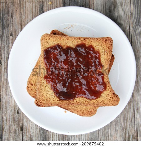Toast with jam Toast with berries jam on white plate - stock photo