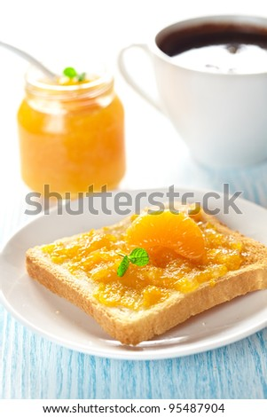 Toast with mandarin marmalade, slice fresh fruit, mint and coffee for breakfast