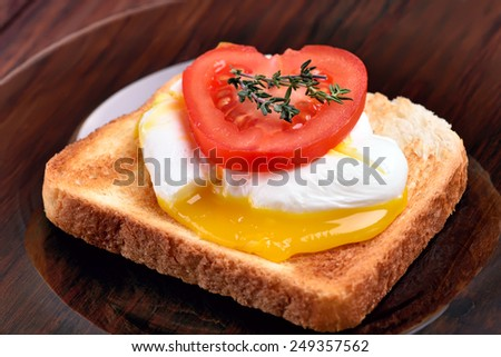 Toast with poached egg and tomato slice, close up view - stock photo