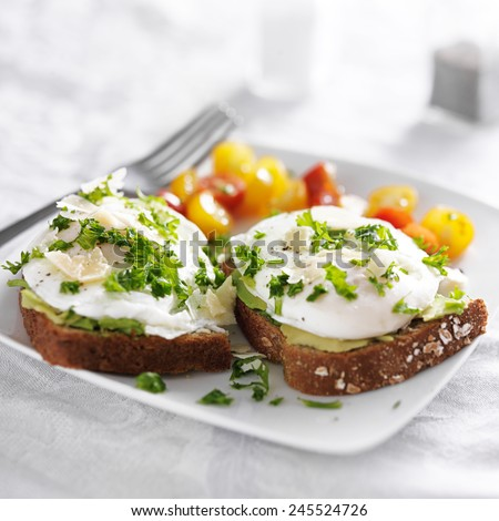 toast with poached eggs, avocado and tomatoes - stock photo
