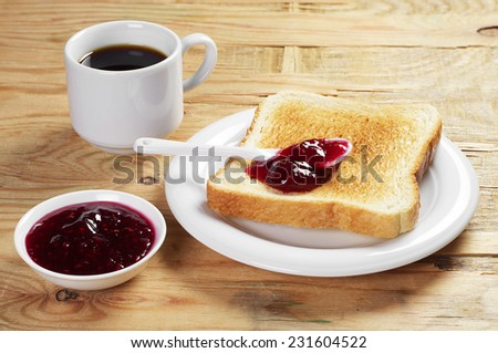 Toast with raspberry jam and cup of hot coffee on old wooden table - stock photo