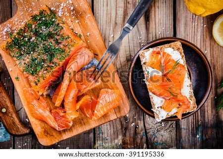 Toast with smoked salmon on wooden table - stock photo