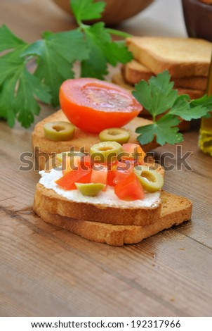 toast with tomato, oil, green olives on wooden table