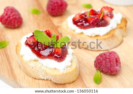 Toasted baguette with cream cheese, raspberry jam, raspberry and mint on a wooden board close-up - stock photo