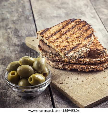 toasted bread and olives on table in close up - stock photo