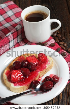 Toasted bread with canned cherries, strawberries and cup of coffee on rustic wooden table