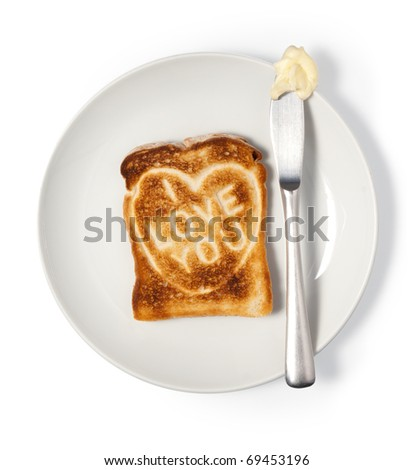 Toasted bread with love message on plate. Isolated on white, Clipping path. - stock photo