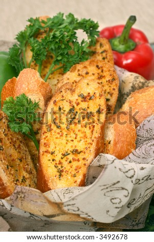 Toasted garlic bread in a basket with capsicums and parsley laid on a checkered mat. - stock photo