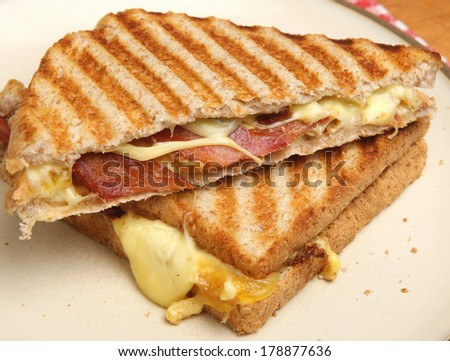 Toasted sandwich with bacon, egg and cheese - stock photo
