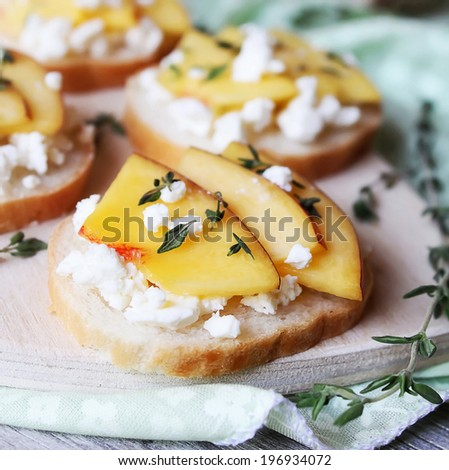 Toasted wheat bread with ripe peaches, crumbled feta or cottage cheese, honey and thyme for snack or summer picnic - stock photo