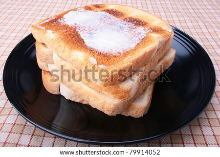 Toasted white bread with butter on a black plate. - stock photo