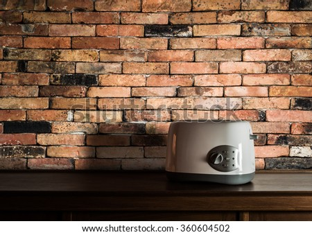 Toaster on wooden cupboard in kitchen room with vintage brick wall background - stock photo