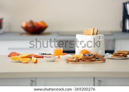 Toaster with dishes, sandwiches and oranges on a light kitchen table - stock photo