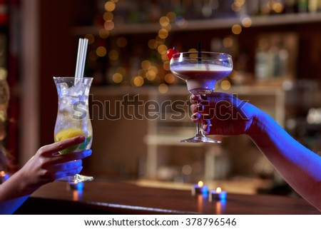 Toasting friendship with colorful drinks in night club - stock photo
