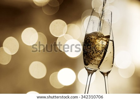 Toasting with champagne glasses against holiday lights - stock photo