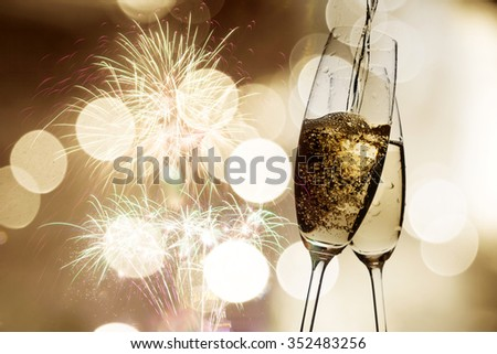 Toasting with champagne glasses against holiday lights, fireworks and clock at midnight - stock photo