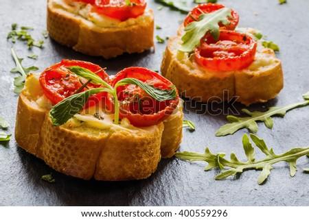 Toasts (Crostini) with ricotta, cherry tomatoes and arugula on black background.  - stock photo