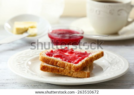 Toasts with jam on plate with cup of tea on light background - stock photo