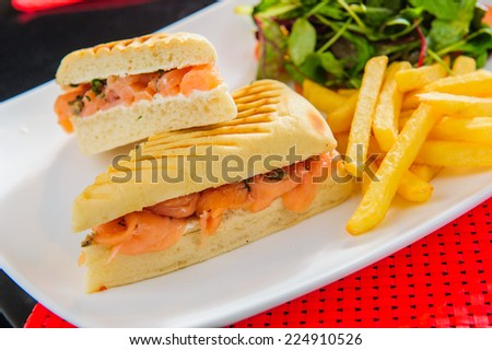 Toasts with red salmon served with french fries and salad. - stock photo