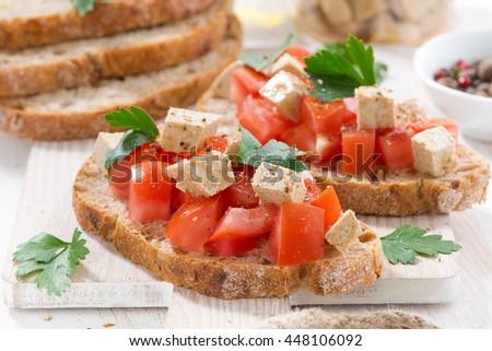 toasts with tomatoes and marinated feta, closeup, horizontal - stock photo