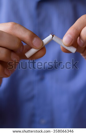 Tobacco addiction. Nicotine smoke. Man brakes cigarette. Unhealthy, danger, bad, narcotic habit. White filter. Health risk, cancer illness. Quit, stop toxic drug. Lifestyle concept. Pack in hand. - stock photo