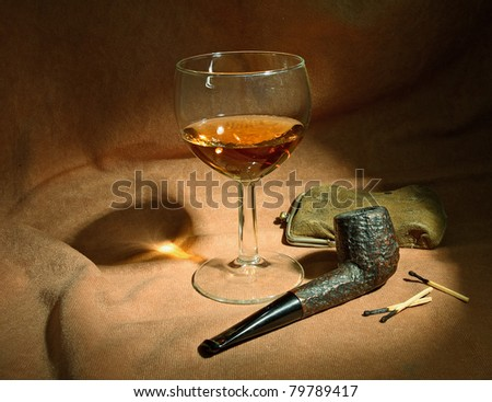 Tobacco pipe and glass of whiskey on brown background
