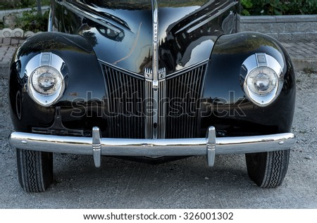 TOBERMORY, ONTARIO - SEPTEMBER 26: Front view of a vintage black Ford automobile with chrome grille and bumper, photographed in Tobermory on Sept 26, 2015 . - stock photo
