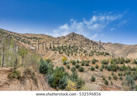 Tochal mountain with rocks and trees in autumn against blue sky, Tehran, Iran. Tochal is a popular recreational region for Tehran's residents