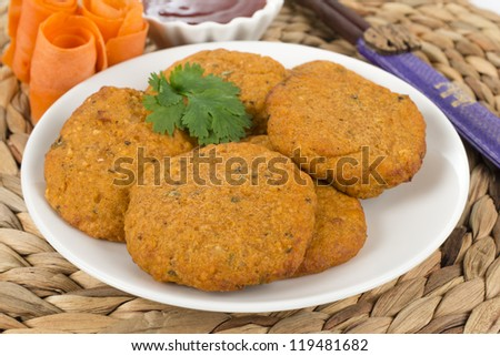 Tod Man Pla - Thai fried fishcakes served with a bowl of sweet chili sauce and garnished with coriander leaves and sliced carrots.