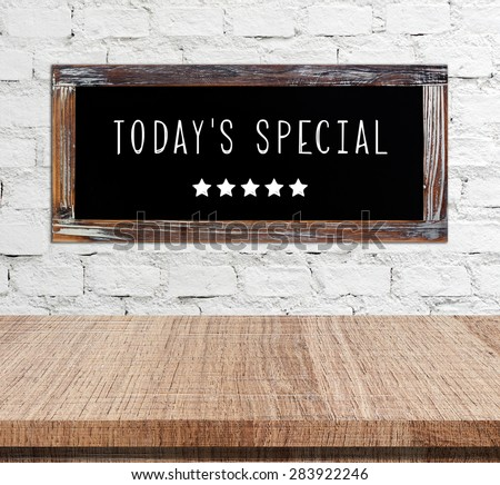 Today's special on vintage chalk board over cement wall and empty wood table background, food and drinks, food display montage - stock photo