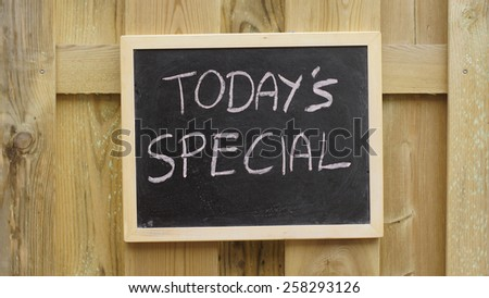 Today's special written on a chalkboard hanging at a wooden wall - stock photo