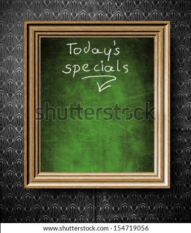 Todays special menu with copy-space chalkboard in old wooden frame on vintage wall - stock photo