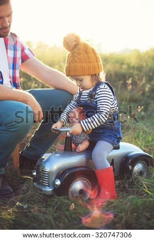 Toddler and father playing with toy in the garden - stock photo
