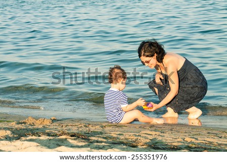 Toddler and his mother playing on the beach at the edge of the water. Photo with untraditional color rendering for artistic look. - stock photo