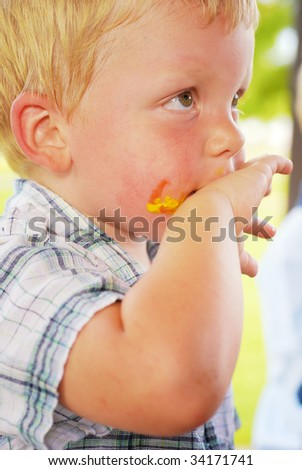 Toddler at a picnic with ketchup and mustard on face - stock photo