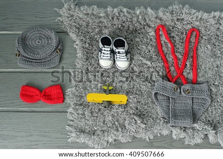 Toddler baby cap, shoes, bowtie, panties and plane lying on the fur blanket with short pile on the wooden floor. Newborn or pregnancy concept - stock photo