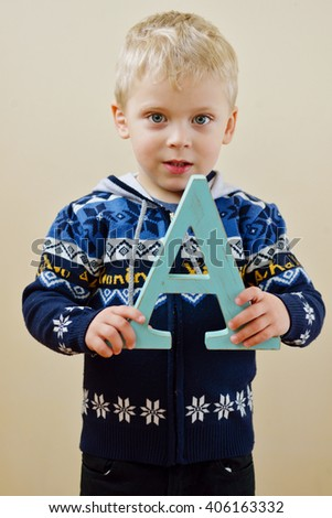 toddler blonde  boy  with a wooden letter A - stock photo