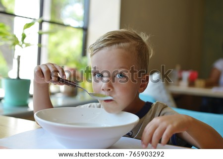 toddler blue-eyed boy eating soup with spoon