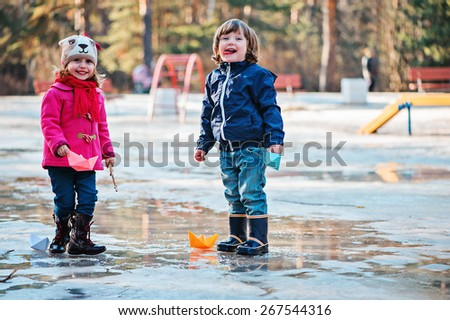 toddler boy and girl are happy together playing in spring puddle with paper boats - stock photo