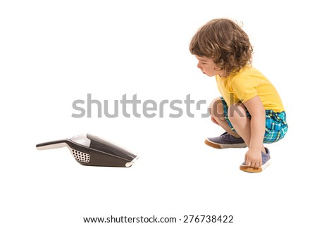 Toddler boy being amazed by hand-held vacuum cleaner isolated on white background - stock photo