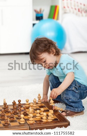 Toddler boy crouching and playing with chess pieces - stock photo