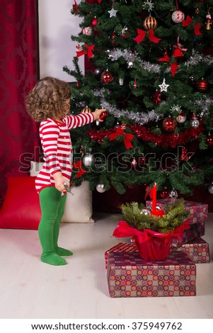 Toddler boy decorate Christmas tree with balls  - stock photo