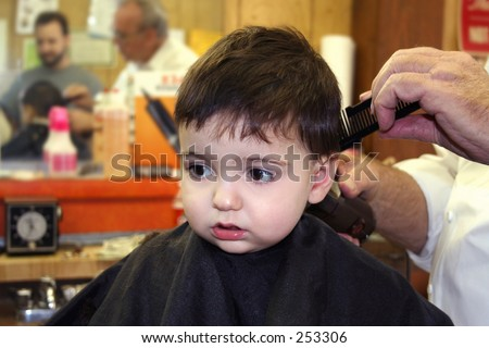 Toddler boy getting his first hair cut at the barbershop. - stock photo