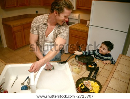 Toddler boy helping dad do the dishes.  Focus on man smiling.